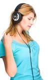 Belle fille avec des écouteurs d'isolement sur le blanc Photos stock