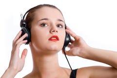 Belle fille avec des écouteurs d'isolement sur un fond blanc photo libre de droits