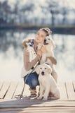 Belle fille avec des animaux familiers près du lac Photo stock