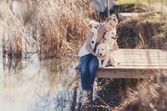 Belle fille avec des animaux familiers près du lac Images stock