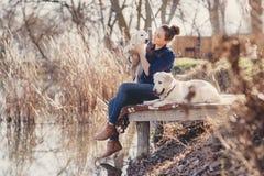 Belle fille avec des animaux familiers près du lac Photos stock