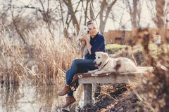 Belle fille avec des animaux familiers près du lac Image stock