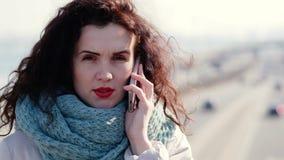 Belle fille avec des boucles parlant au téléphone tout en se tenant sur le pont Conduire des voitures à l'arrière-plan banque de vidéos