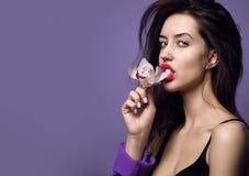 Belle fille avec des fleurs d'orchidée Visage de femme de modèle de beauté sur le fond pourpre photo stock