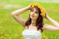 Belle fille avec des fleurs de pissenlit dans le domaine vert images stock