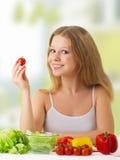 Belle fille avec des légumes dans la cuisine Photographie stock libre de droits