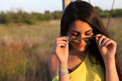 Belle belle fille avec des lunettes de soleil et des clous bleus images stock
