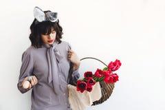 Belle fille avec des oreilles de lapin tenant les oeufs et les tulipes en bois de Pâques dans le panier rustique sur le fond blan images libres de droits