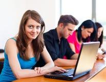 Belle fille avec l'ordinateur portable à l'école Images libres de droits