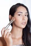 Belle fille avec la brosse de maquillage sur son visage Photos stock
