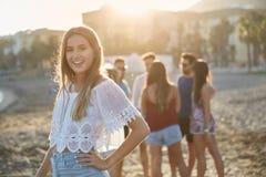 Belle fille avec la main sur la hanche se tenant sur la plage avec les amis b Image stock