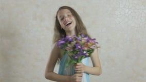 Belle fille avec le bouquet de rire de fleurs banque de vidéos