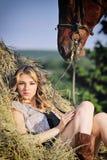 Belle fille avec le cheval de châtaigne dans la pile de foin Images libres de droits