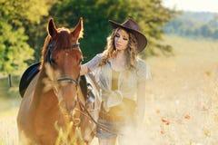 Belle fille avec le cheval de châtaigne dans le domaine de soirée Photo libre de droits