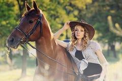 Belle fille avec le cheval de châtaigne dans le domaine de soirée Photo stock