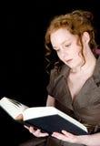 Belle fille avec le cheveu rouge affichant un livre Image stock