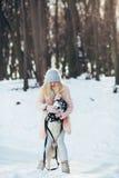 Belle fille avec le chien de traîneau de chien en bois neigeux Image stock