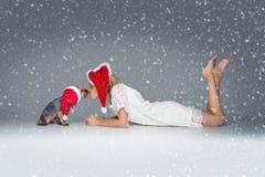 Belle fille avec le chien de yorkie dans le chapeau de Santa Image stock