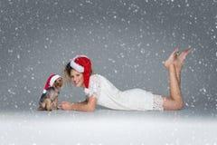 Belle fille avec le chien de yorkie dans le chapeau de Santa Photographie stock libre de droits
