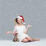 Belle fille avec le chien de yorkie dans le chapeau de Santa Images libres de droits