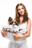 Belle fille avec le chien mignon de papillon sur le blanc d'isolement Image stock