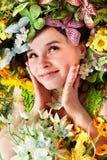 Belle fille avec le guindineau et la fleur sur l'herbe. Photographie stock libre de droits