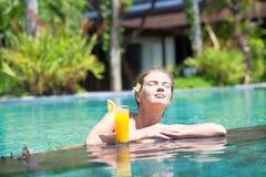Belle fille avec le jus d'orange dans la piscine de luxe Photos libres de droits