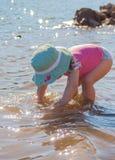 Belle fille avec le maillot de bain et le chapeau jouant sur la rive avec de l'eau image libre de droits