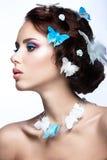 Belle fille avec le maquillage bleu lumineux et papillons dans ses cheveux Photographie stock