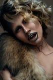 Belle fille avec le maquillage créatif avec de l'or et argent et boucles Modèle avec la fourrure et les lèvres foncées lumineuses Image libre de droits