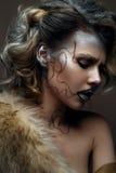 Belle fille avec le maquillage créatif avec de l'or et argent et boucles Modèle avec la fourrure et les lèvres foncées lumineuses Photos stock