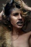 Belle fille avec le maquillage créatif avec de l'or et argent et boucles Modèle avec la fourrure et les lèvres foncées lumineuses Photographie stock libre de droits