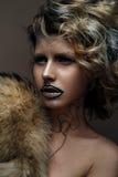 Belle fille avec le maquillage créatif avec de l'or et argent et boucles Modèle avec la fourrure et les lèvres foncées lumineuses Photo stock
