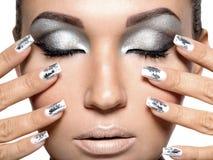 Belle fille avec le maquillage et les clous argentés Images stock