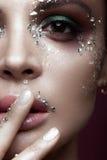 Belle fille avec le maquillage lumineux de couleur et cristaux sur le visage Portrait en gros plan Photos libres de droits