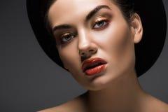 belle fille avec le maquillage posant dans le chapeau de feutre noir pour la pousse de mode photo libre de droits