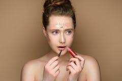 Belle fille avec le rouge à lèvres dans les mains et le maquillage de tresse Photo stock
