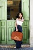 Belle fille avec le sac de vintage contre la porte verte Image stock