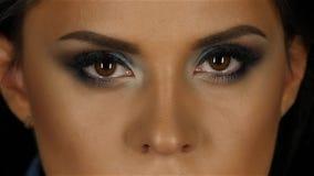 Belle fille avec le souffle de maquillage prenant des regards directement et des lueurs ses yeux Fin vers le haut banque de vidéos