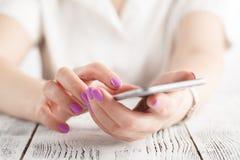 Belle fille avec le téléphone portable moderne dans des mains photos stock