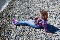 Belle fille avec le téléphone se reposant sur la plage rocheuse Images libres de droits