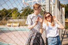 Belle fille avec les cheveux blonds dans des lunettes de soleil se penchant sur la barrière de maille avec le garçon frais regard Photo stock
