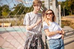 Belle fille avec les cheveux blonds dans des lunettes de soleil se penchant sur la barrière de maille avec le garçon frais se ten Images stock