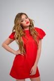 Belle fille avec les cheveux blonds onduleux dans la pose rouge de robe Images libres de droits