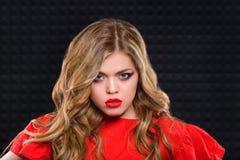 Belle fille avec les cheveux blonds onduleux dans la robe rouge Image libre de droits