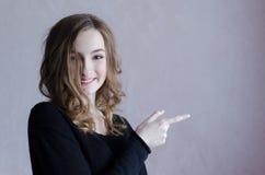Belle fille avec les cheveux bouclés indiquant le côté photo libre de droits