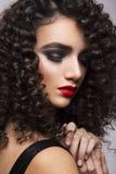 Belle fille avec les cheveux bruns bouclés et les lèvres rouges Photos stock