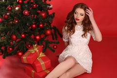 Belle fille avec les cheveux foncés dans la robe élégante avec le grand cadeau de Noël Photographie stock