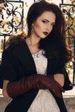 Belle fille avec les cheveux foncés dans le manteau élégant et les gants en cuir photographie stock libre de droits