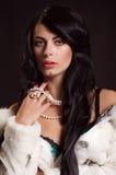 Belle fille avec les cheveux foncés dans un manteau de fourrure blanc Image libre de droits